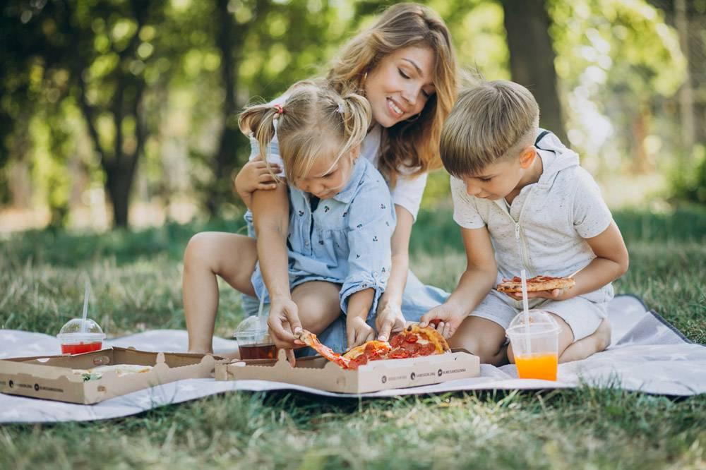 母亲带着儿子和女儿在公园里吃披萨_10298469