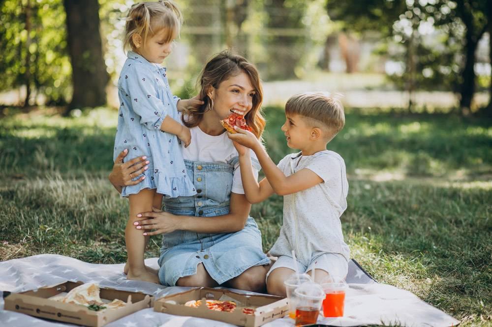 母亲带着儿子和女儿在公园里吃披萨_10298474