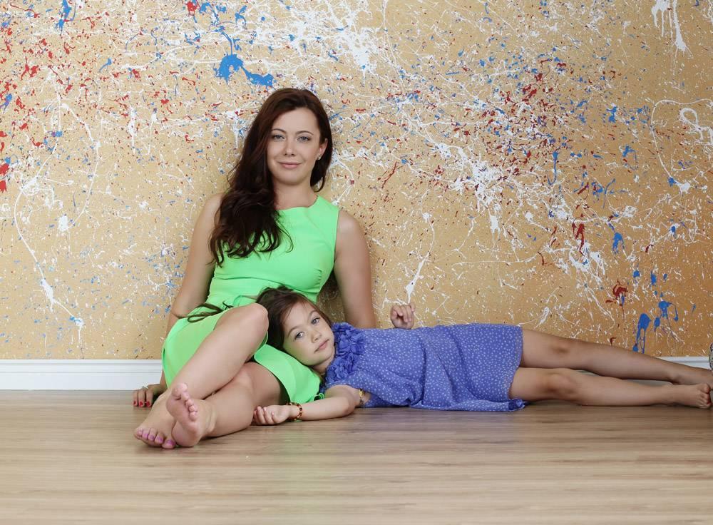 母亲带着女儿在地板上摆姿势_10446419