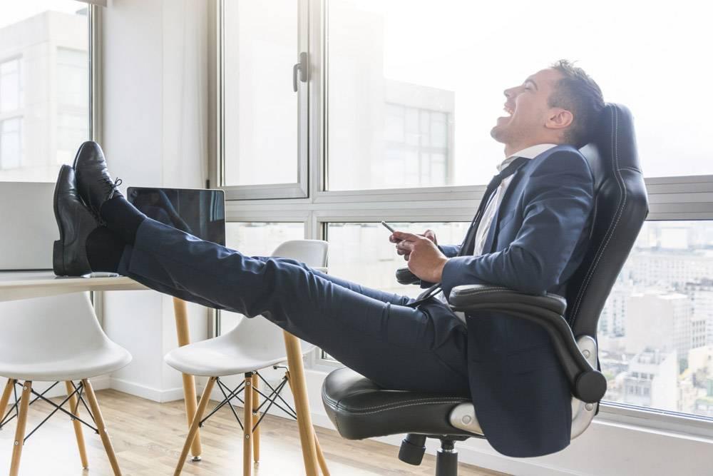 快乐的商人坐在工作场所的椅子上使用手机_3149723