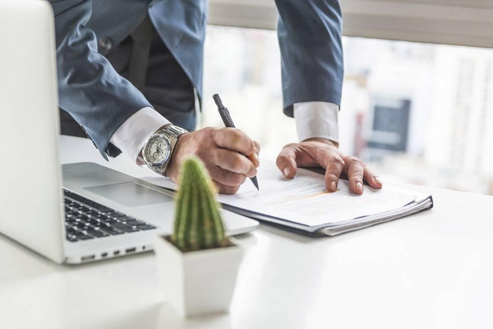 商人用笔记本电脑在办公桌上用钢笔在文件上_3165848