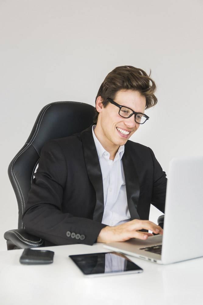 快乐的商人在办公室用笔记本电脑工作_2627345