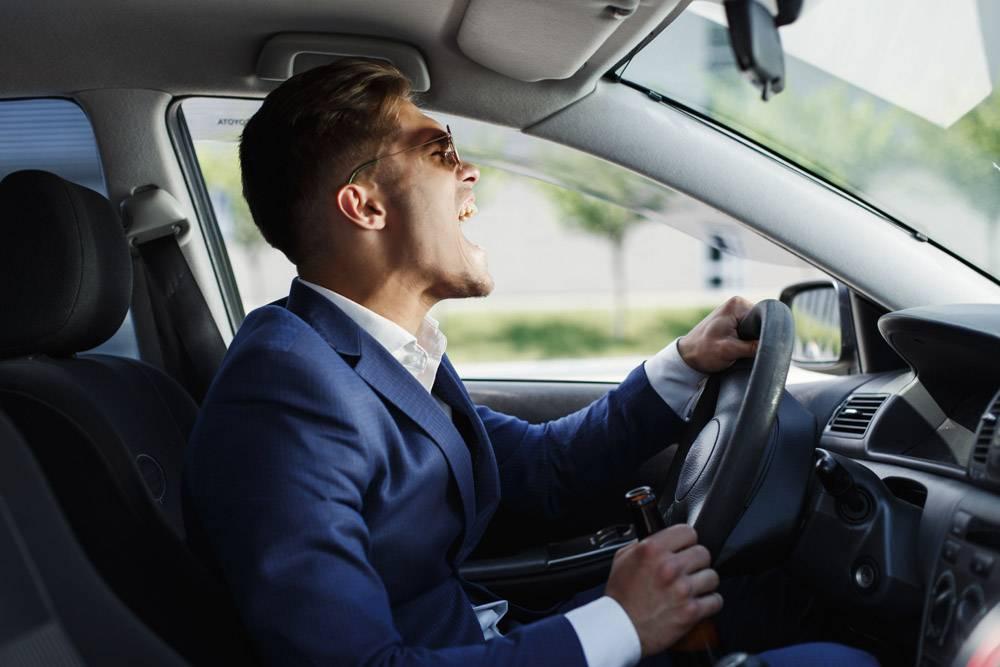 快乐的商人坐在车内的方向盘前展示他的情绪_2612720