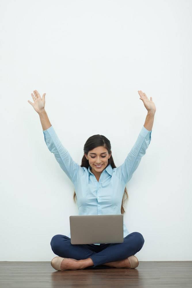 快乐的年轻女子在地板上用笔记本电脑工作_992869