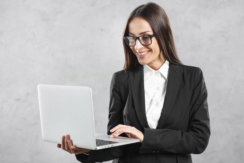 微笑的女商人看着手中的笔记本电脑靠在水泥_3956672