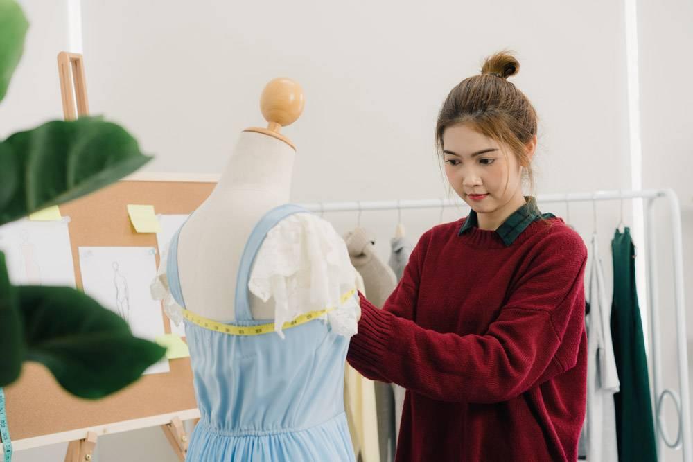 專業漂亮的亞洲女時裝設計師在人體模型服裝_3441229