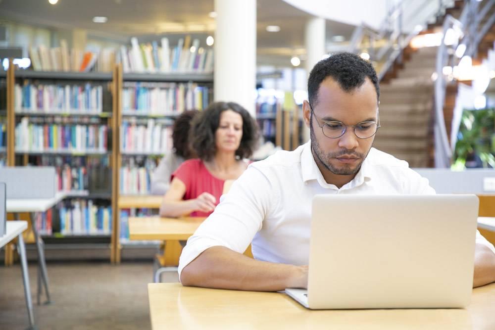 專注于在教室里使用計算機的成年男性學生_5890277