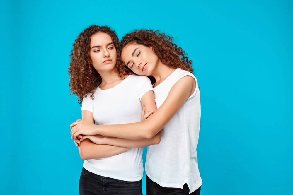 两个年轻漂亮的双胞胎拥抱在一起越过蓝色_9321974