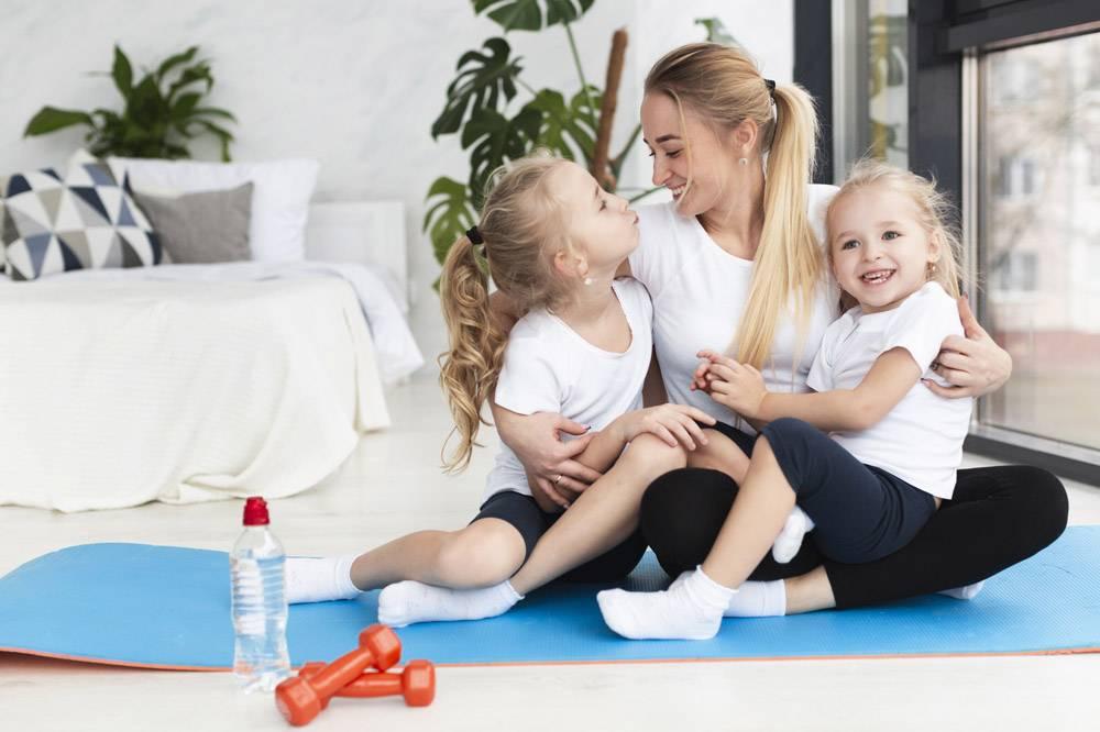 快乐的母亲与女儿在家中瑜伽垫上合影_7435879