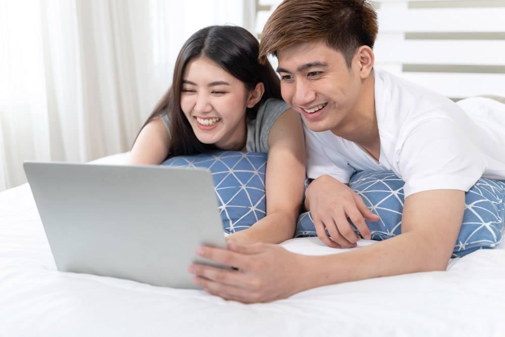 快乐的年轻美女和帅哥在家里卧室的床上使用_5389032