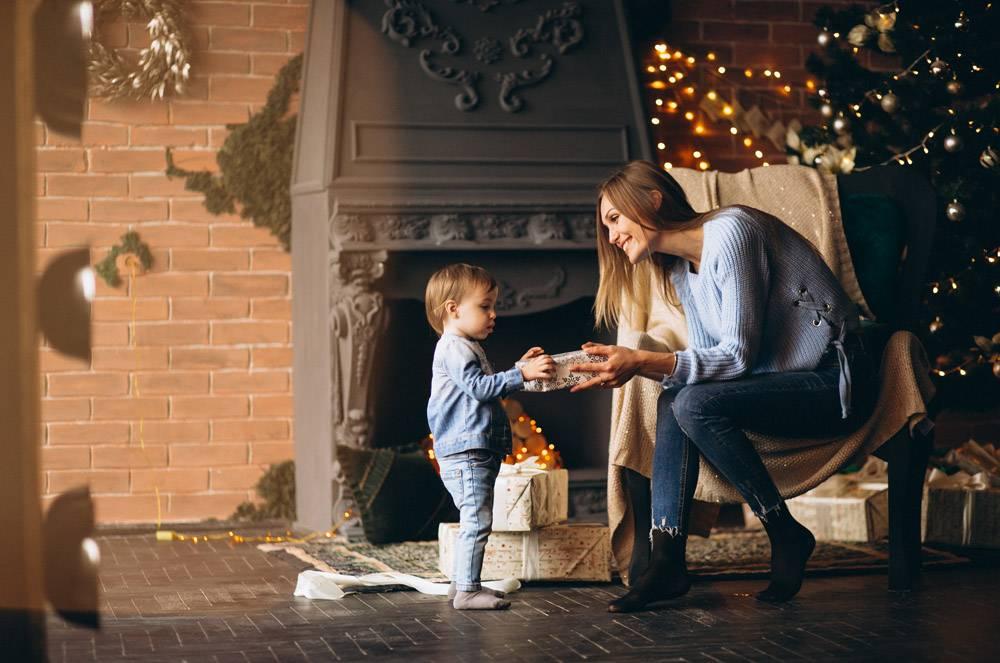 母亲带着女儿坐在圣诞树旁的椅子上_3655263