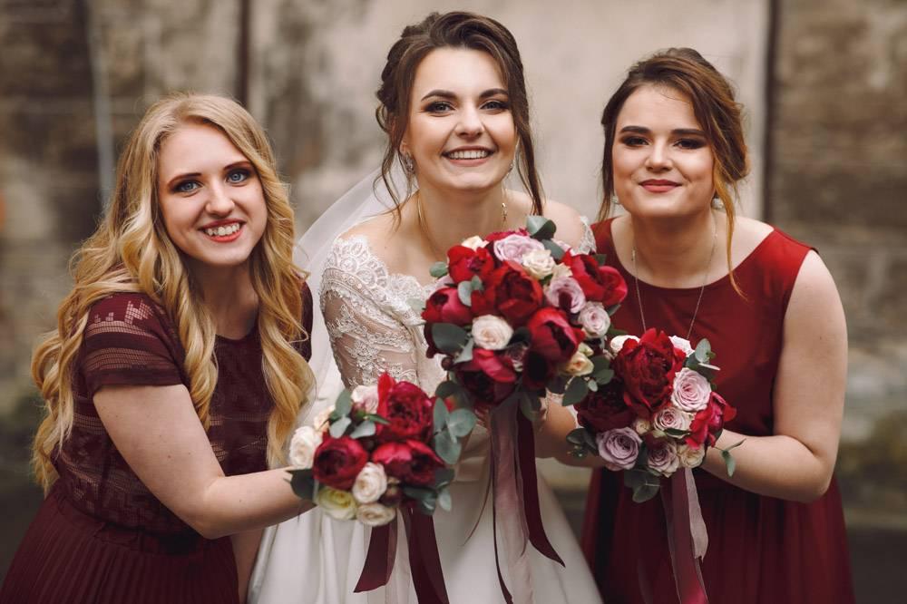 身穿红色礼服的新娘和伴娘在外面潮湿的老街_2612633