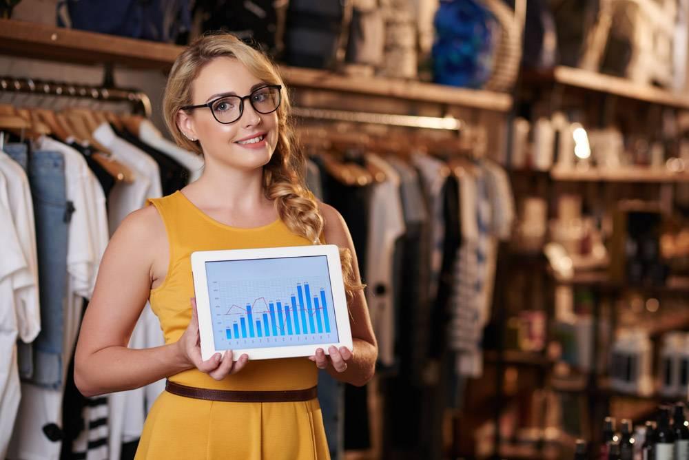 站立在精品店的年轻白种人妇女和显示有企业_5839659