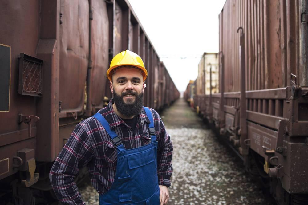 站立在货车之间看到水元波的微笑的铁路工作者画象_11136335