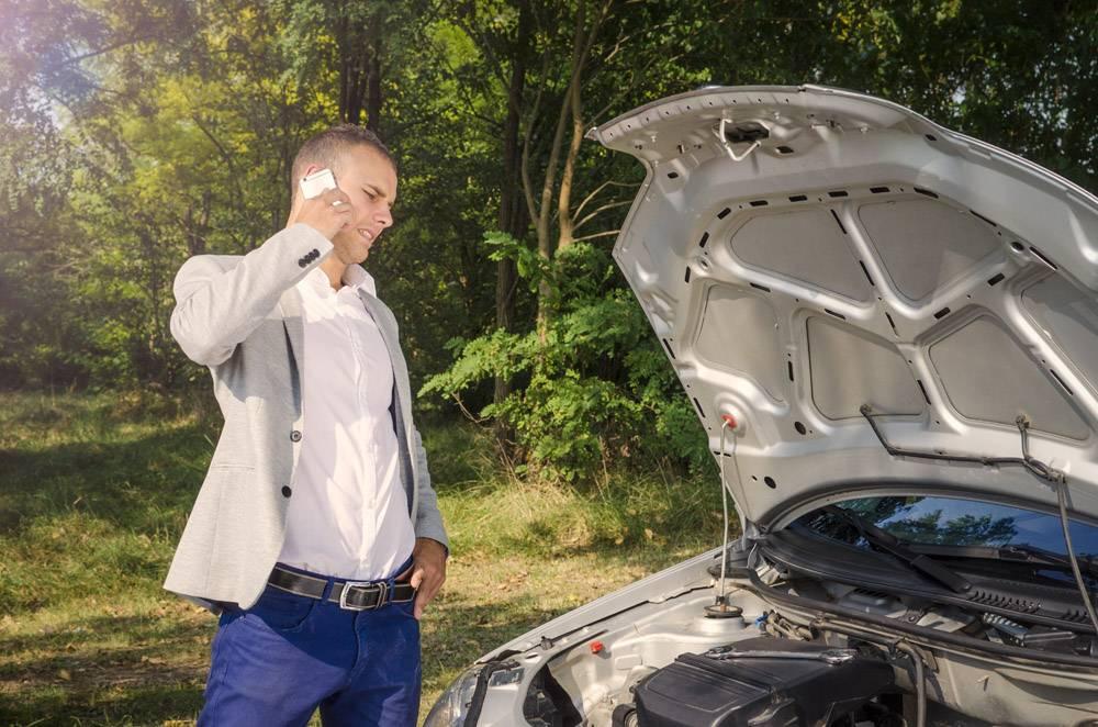 站立由打开的敞篷的人打电话找死小子和试图修理血液不断地从他车辆哦_11136111